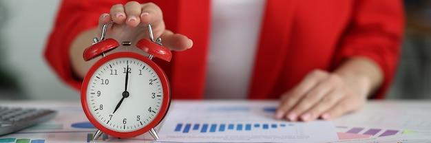 Kobieta w czerwonej kurtce wyłączając budzik w koncepcji zarządzania czasem zbliżenie stołu