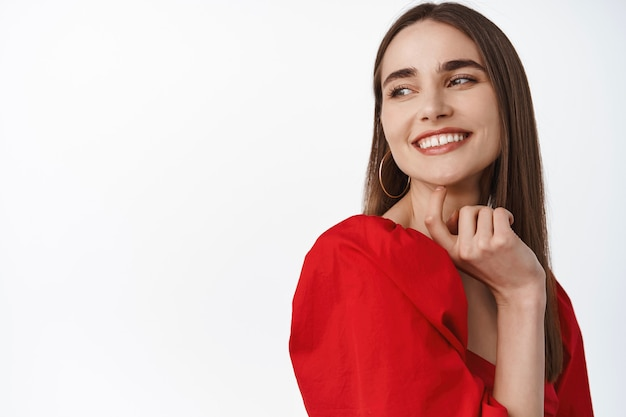 Kobieta w czerwonej romantycznej sukience, uśmiechnięta i patrząca w lewo z zadowolonym, szczęśliwym uśmiechem, stojąca na białym