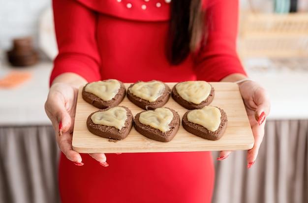 Kobieta w czerwonej sukience dokonywanie valentine ciasteczka w kuchni