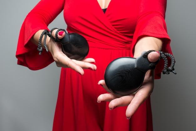 Kobieta w czerwonej sukience gra kastaniety flamenco sewilli