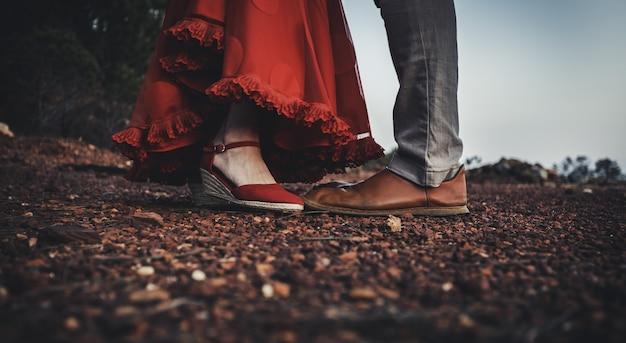 Kobieta w czerwonej sukience i butach przed mężczyzną