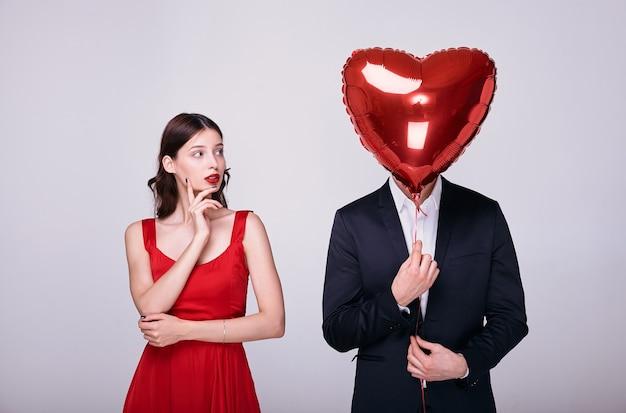Kobieta w czerwonej sukience i mężczyzna w garniturze trzyma balon w kształcie czerwonego serca nad twarzą na białym tle