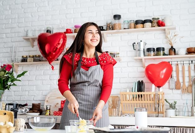 Kobieta w czerwonej sukience i szarym fartuchu dokonywanie valentine ciasteczka w kuchni