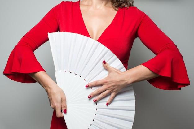 Kobieta w czerwonej sukience macha białym fanem flamenco sevillanas