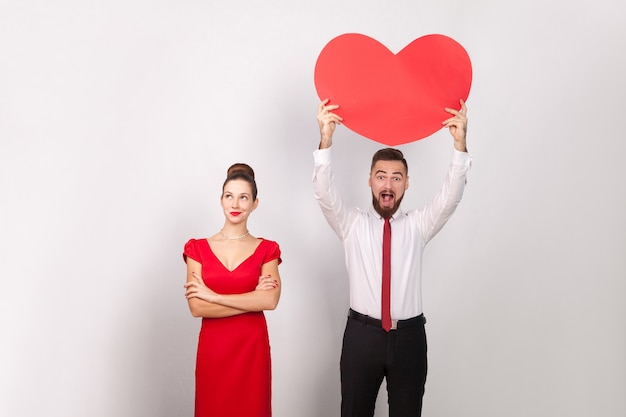 Kobieta w czerwonej sukience myślenia, szczęście człowiek posiadający czerwone serce. wewnątrz, studio strzał, na białym tle na szarym tle