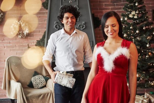 Kobieta w czerwonej sukience otrzyma teraz prezent świąteczny od chłopaka.