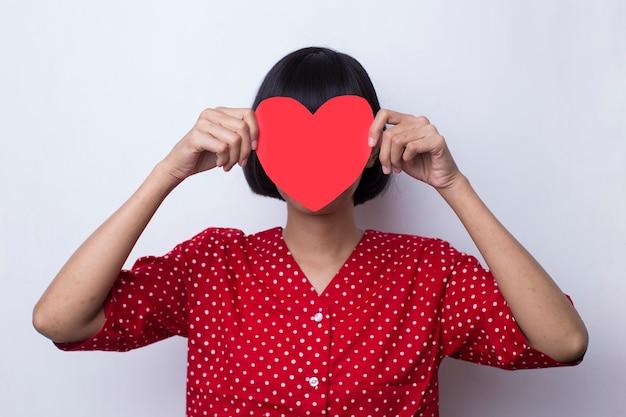 Kobieta w czerwonej sukience pokazuje kształt serca w koncepcji miłości i walentynek