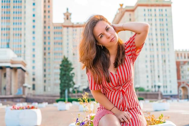 Kobieta w czerwonej sukience pozuje w przestrzeni głównego uniwersytetu rosji w moskwie