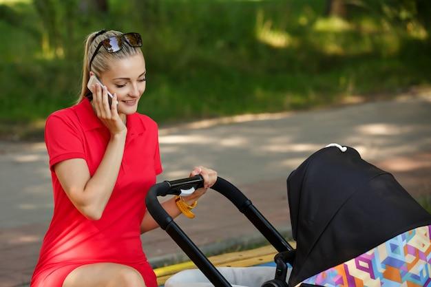 Kobieta w czerwonej sukience rozmawia przez telefon w parku