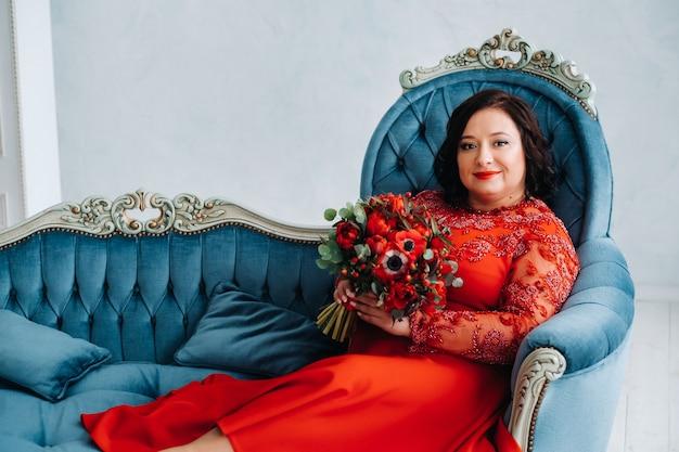 Kobieta w czerwonej sukience siedzi na kanapie i trzyma bukiet czerwonych róż i truskawek we wnętrzu.