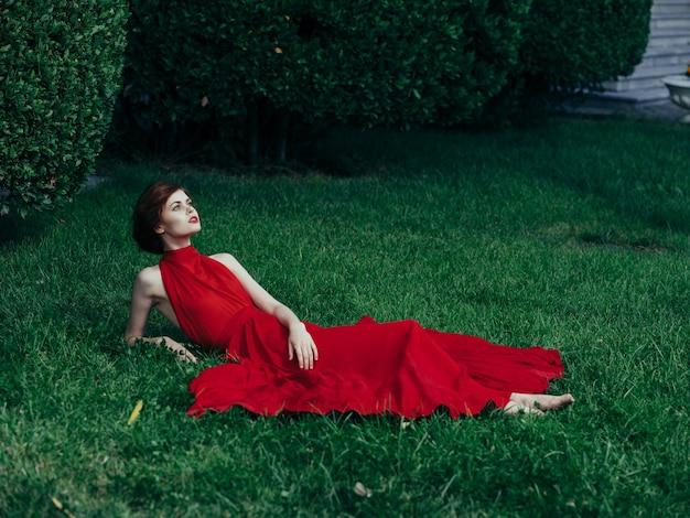 Kobieta w czerwonej sukience siedzi na uroku trawy i luksusowym parku w egzotycznym stylu.