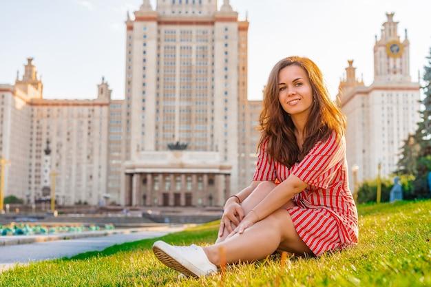 Kobieta w czerwonej sukience siedzi na zielonej trawie przed głównym wieżowcem uniwersytetu moskiewskiego