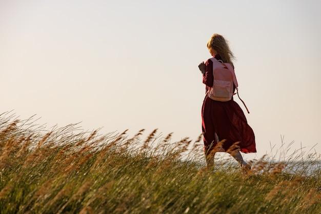 Kobieta w czerwonej sukience spaceruje brzegiem morza o wschodzie słońca.
