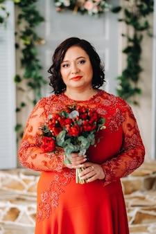 Kobieta w czerwonej sukience stoi i trzyma we wnętrzu bukiet czerwonych róż i truskawek.