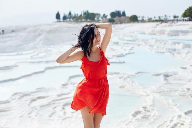 Kobieta w czerwonej sukience stoi na białych trawertynach. kobieta w słońcu w pobliżu białej ściany. pamukkale