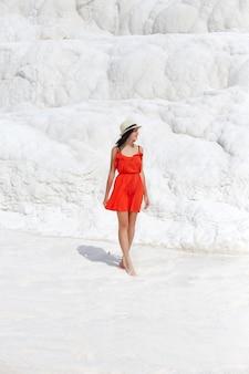 Kobieta w czerwonej sukience stoi na białych trawertynach