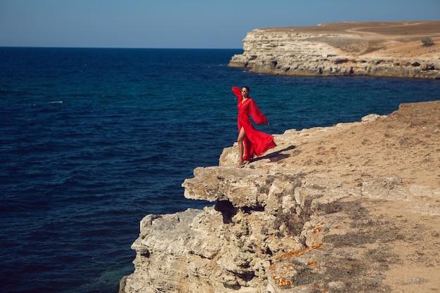 Kobieta w czerwonej sukience stoi na klifie w pobliżu morza na klifie latem