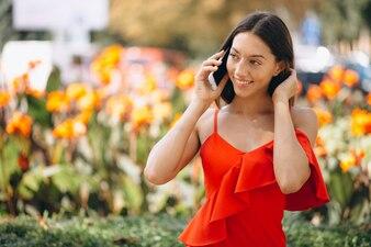 Kobieta w czerwonej sukience za pomocą telefonu