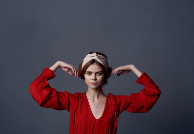 Kobieta w czerwonej sukni dekoracji urok ciemne tło