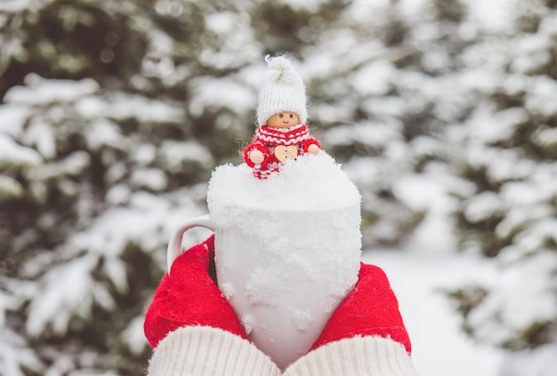 Kobieta w czerwonych rękawiczkach trzyma kubek ze śniegiem i uroczą świąteczną zabawką w środku.