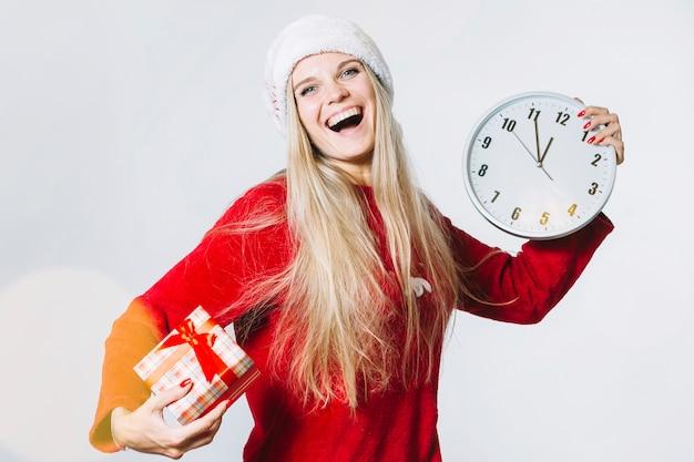 Kobieta w czerwonych ubraniach z zegarem i małym prezenta pudełkiem