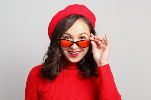 Kobieta w czerwonych ubraniach zdejmując okulary patrząc w kamerę.