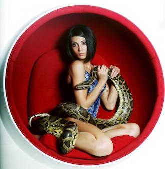 Kobieta w czerwonym fotelu holdung python