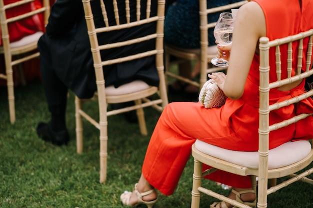 Kobieta w czerwonym garniturze siedzi na krześle wśród gości na trawniku od tyłu