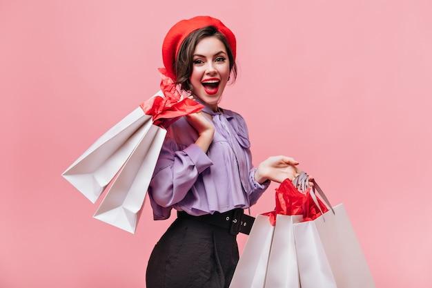 Kobieta w czerwonym kapeluszu, czarnych spodniach i lekkiej bluzce śmieje się i pozuje z paczkami po zakupach.