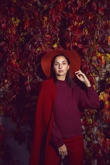 Kobieta w czerwonym kapeluszu i czerwonym swetrze stoi na tle pomarańczowych liści ściany winogron jesienią