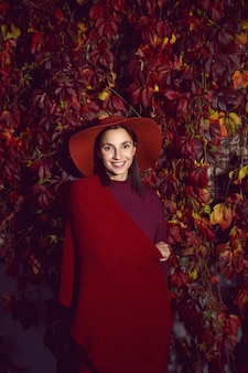 Kobieta W Czerwonym Kapeluszu I Czerwonym Swetrze Stoi Na Tle Pomarańczowych Liści ściany Winogron Jesienią Premium Zdjęcia