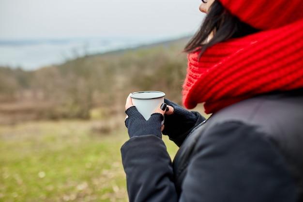 Kobieta w czerwonym kapeluszu i szaliku, picie herbaty z metalowego kubka na świeżym powietrzu, koncepcja podróży, jesienny krajobraz tła.