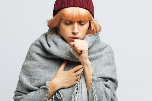 Kobieta w czerwonym kapeluszu kaszel, czując pierwsze objawy choroby. zapalenie oskrzeli,