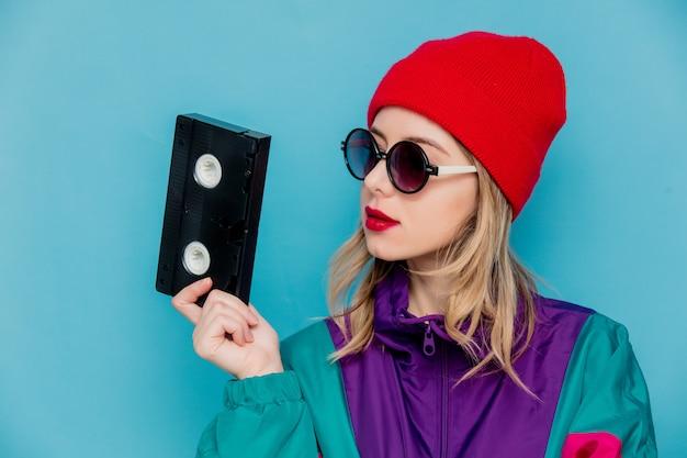 Kobieta w czerwonym kapeluszu, okulary przeciwsłoneczne i garnitur z lat 90. z kasetą vhs