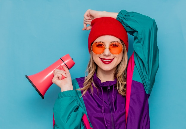Kobieta w czerwonym kapeluszu, okulary przeciwsłoneczne i kostium z lat 90. z głośnikiem