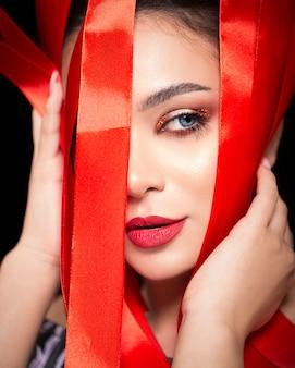 Kobieta w czerwonym makijażu z czerwoną wstążką