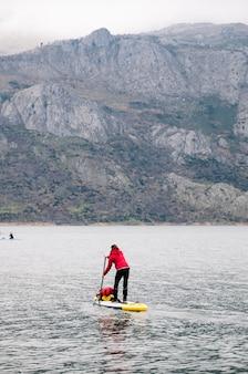Kobieta w czerwonym płaszczu ćwiczy wiosłowanie po górskim jeziorze z bagażem na desce