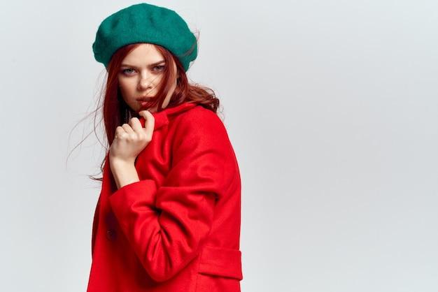 Kobieta w czerwonym płaszczu i zielonym kapeluszu na białym tle