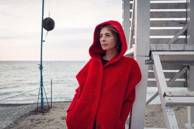 Kobieta w czerwonym płaszczu stoi nad brzegiem morza, oparta o drewnianą konstrukcję.