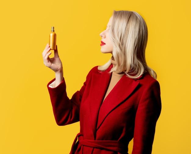 Kobieta w czerwonym płaszczu z perfumami na żółtej ścianie