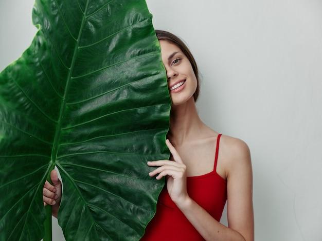 Kobieta w czerwonym stroju kąpielowym tropikalnych liści palmowych na białym tle