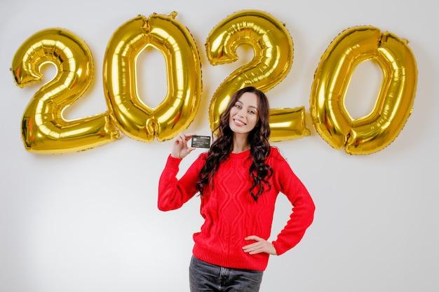Kobieta w czerwonym swetrze gospodarstwa szablon karty kredytowej przed balonami nowy rok 2020