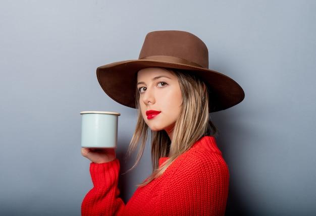 Kobieta w czerwonym swetrze i kapeluszu z filiżanką kawy