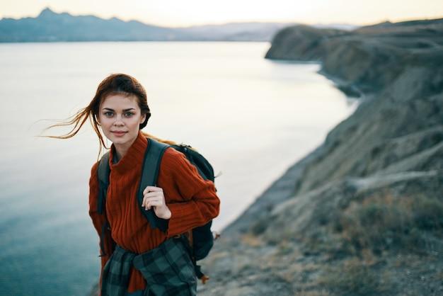 Kobieta w czerwonym swetrze na zewnątrz w górach świeże powietrze morze krajobraz gór