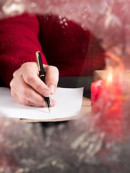 Kobieta w czerwonym swetrze pisze list do koperty za zamarzniętym szkłem. przerwa świąteczna.
