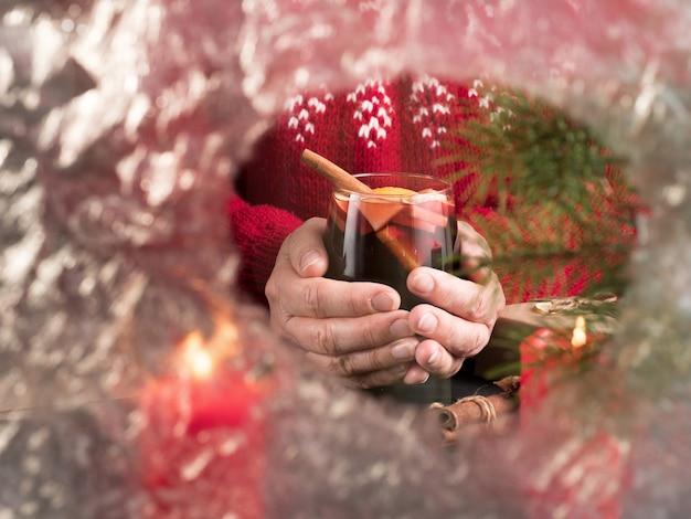 Kobieta w czerwonym swetrze trzyma kieliszek grzanego wina za zamrożonym kieliszkiem. przerwa świąteczna.
