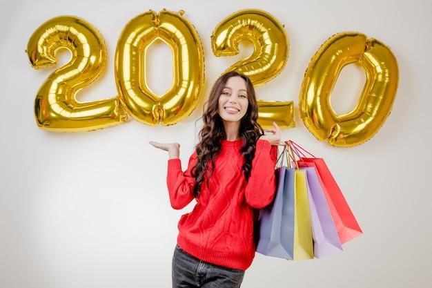 Kobieta w czerwonym swetrze trzyma kolorowe torby na zakupy przed balonami nowego roku 2020