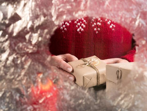 Kobieta w czerwonym swetrze trzyma prezenty za mrożonym szkłem. przerwa świąteczna.