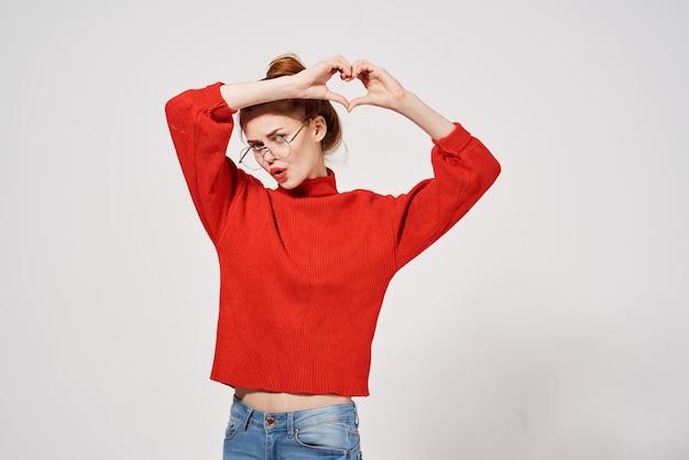 Kobieta w czerwonym swetrze trzyma ręce przed jej okulary zabawny makijaż.