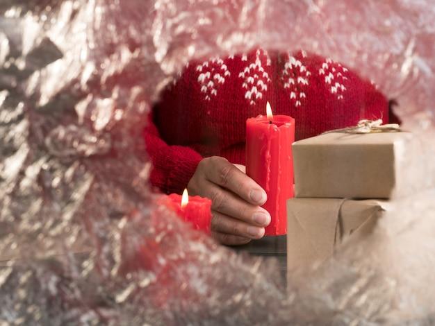 Kobieta w czerwonym swetrze trzyma świecę za zamarzniętym szkłem. przerwa świąteczna.